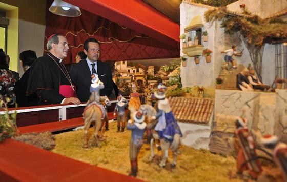 El arzobispo recibe las explicaciones de Gonzalo Madariaga, propietario de la mayoría de las figuras que se exponen en el nacimiento.  Foto: J. C. Vázquez y Victoria Hidalgo