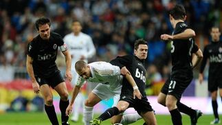 Benzema trata de salir de la presión de tres rivales. / AFP