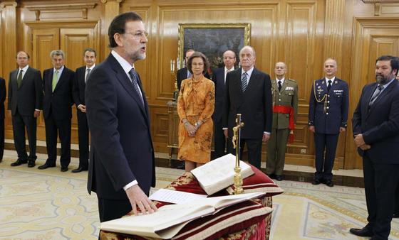 Rajoy pone la mano derecha sobre la Constitución ante Francisco Caamaño, que ha actuado de Notario Mayor del Reino. / EFE