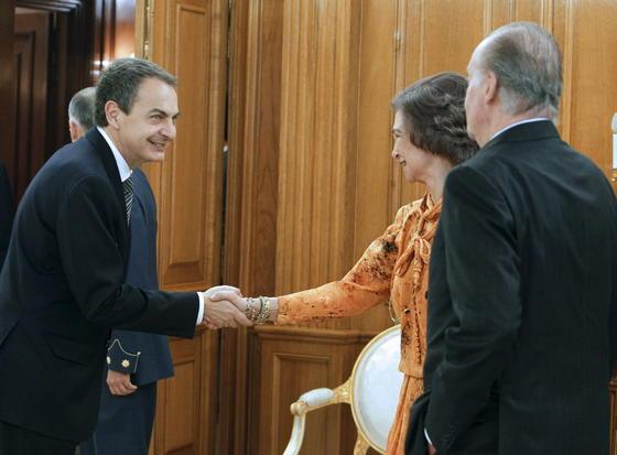 El presidente saliente estrecha la mano a la Reina en presencia del Rey. / EFE