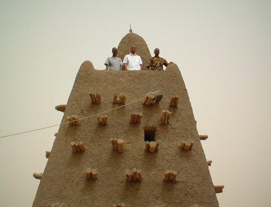 Con camisa blanca, encaramado a una de las torres de la mezquita de Djingareyber, Tombuctú.