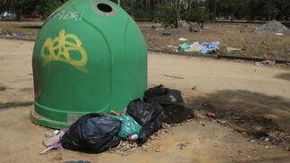 Imagen del contenedor de vidrio, que a sus pies se encuentran bolsas de restos de basura.  Foto: Paco Guerrero