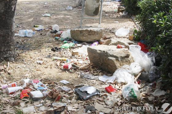 Pláticos y restos de suciedad esparcidos por el suelo del recinto frente a una papelera.  Foto: Paco Guerrero