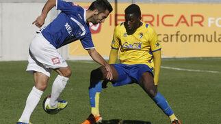 El autor del gol del Melilla, Velasco, intenta un pase ante Moke.   Foto: Julio Gonzalez