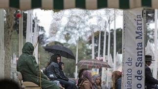 Capeando el temporal. Ya sea con chubasqueros o con paraguas, algunos valientes decidieron plantarle cara ayer al mal tiempo. A pesar de la lluvia y el frío, resistieron en el recinto de Las Banderas para apurar en él las últimas horas de Feria, de la que ya se tuvieron que despedir hasta el año que viene.  Foto: Fito Carreto