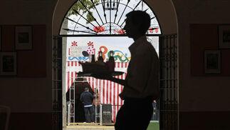 Un camarero porta una bandeja con bebidas dentro de la Caseta Municipal del recinto de Las Banderas.  Foto: Fito Carreto
