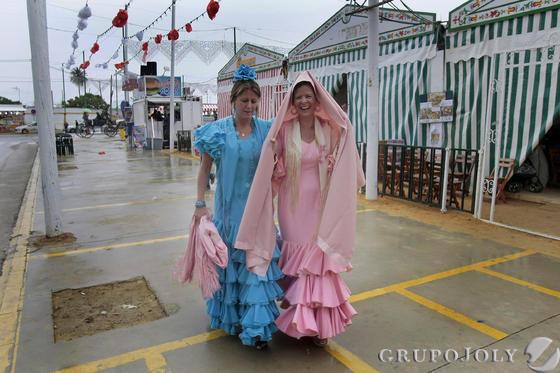 Dos mujeres ataviadas de flamenca se resguardan de la lluvia en una de las desiertas avenidas de Las Banderas durante la jornada de ayer.  Foto: Fito Carreto