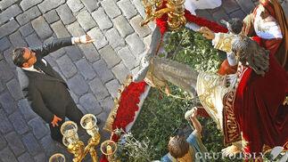 El conocido capataz Martín Gómez dirige las evoluciones del misterio de Cristo Rey durante los primeros compases de la salida procesional.  Foto: Pascual