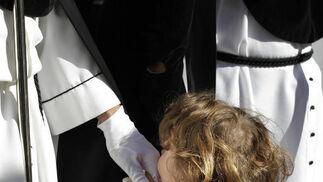 Un pequeño niño coge la mano de un nazareno de la Hermandad de La Coronación de Espinas a su paso por la calle Arcos.  Foto: Migue Angel Gonzalez