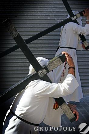 Dos hermanos de El Transporte cargando con sendas cruces de penitencia durante el inicio de la procesión.  Foto: Manuel Aranda