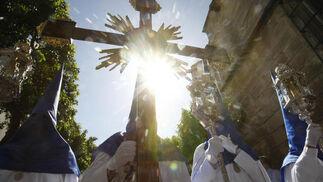 El sol de la tarde, que llegó a pegar con inusitada fuerza, se dibuja en la imagen tras la cruz de guía de la Hermandad de la Borriquita.  Foto: Pascual