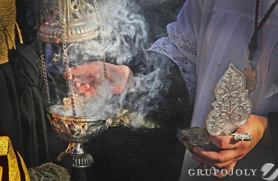 El monaguillo vierte incienso en el incensario antes de que pase el misterio de la cofradía.  Foto: Vanesa Lobo
