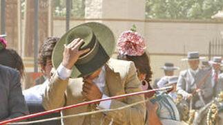 Un cochero se protege la cara con su sombrero del fuerte viento.  Foto: Pascual