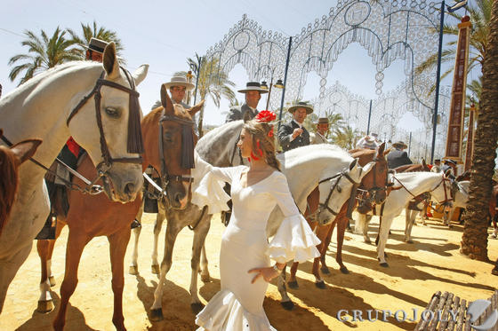 Una joven vestida de flamenca acaricia ayer a uno de los caballos que paseó por el González Hontoria.  Foto: Pascual