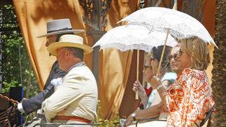 Un grupo se protege del sol con unos paraguas en un carruaje.  Foto: Pascual