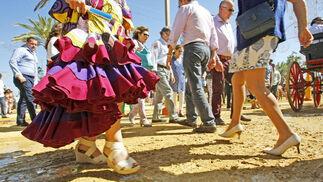 Una mujer vestida de flamenca se remanga el vestido al pasar por una zona enfangada.  Foto: Pascual