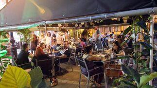 Entregados al 'Superbocapizza'. Una de las señas de identidad del establecimiento Al Trote son sus 'superbocapizza', que el público puede saborear en su terraza, situada en Compositor Serrano Lucena. / Barrionuevo