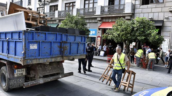 Una cuadrilla de operarios municipales y agentes de la Policía Local retiran veladores el pasado noviembre de la Avenida de la Constitución.