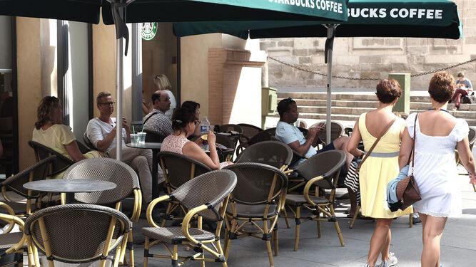 Una pareja de turistas pasa junto a los veladores del Starbucks de la Avenida.