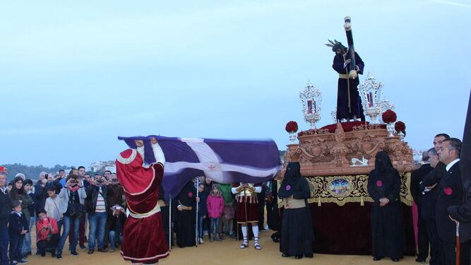 El abanderado revolea la bandera delante del paso de Jesús Nazareno al llegar a la cima del cerro del Calvario.