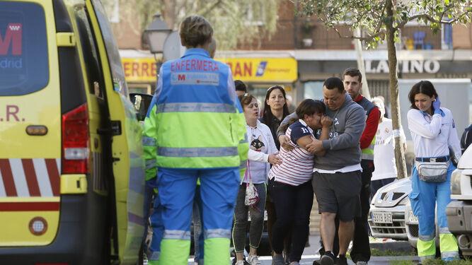 Familiares de las víctimas y sanitarios de los servicios de emergencias, ayer en la puerta del bar en Alcorcón.
