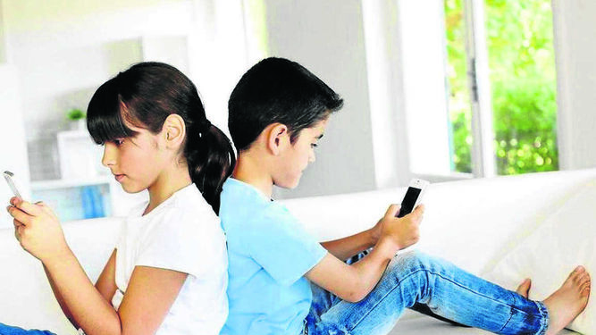Dos menores juegan con sus teléfonos móviles.