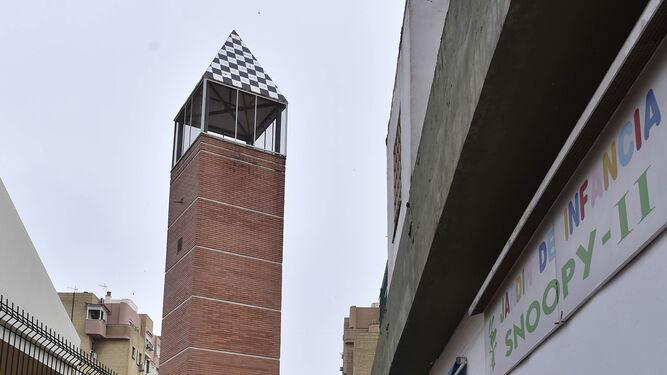 Una mujer y al fondo, la torre de la iglesia Jesús de Nazaret.