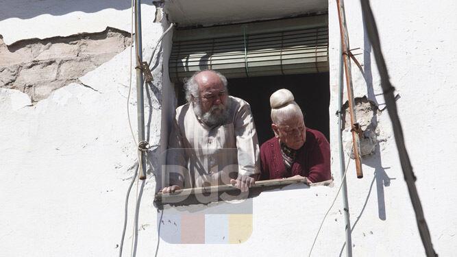 Dos vecinos miran desde una ventana el dispositivo desplegado tras el suceso.