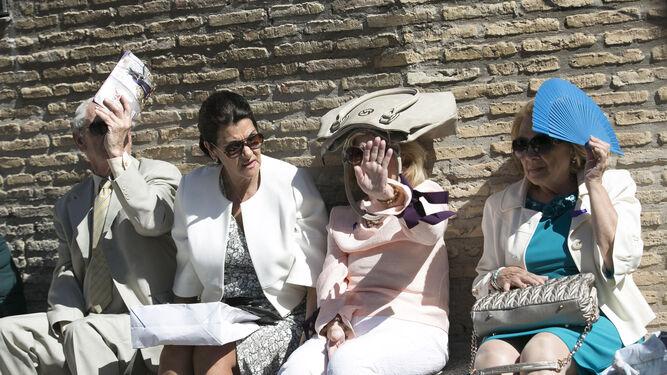 Cuatro personas aguardan la salida de la hermandad de la Hiniesta.