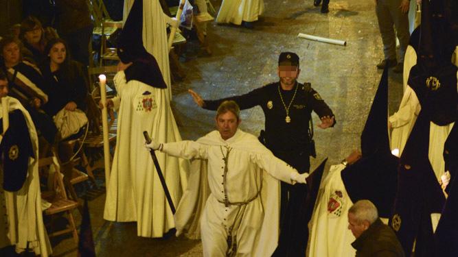 Un diputado de tramo y un Policía Local intentan calmar a los nazarenos de la Macarena en Sierpes.