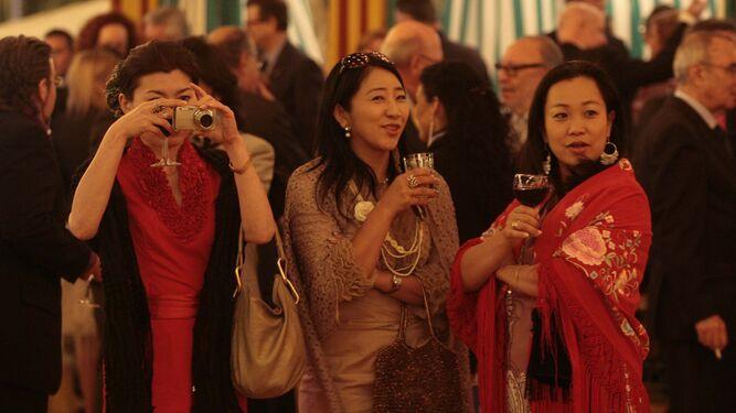 Tres turistas asiáticas, con mantones de  Manila, en una caseta.