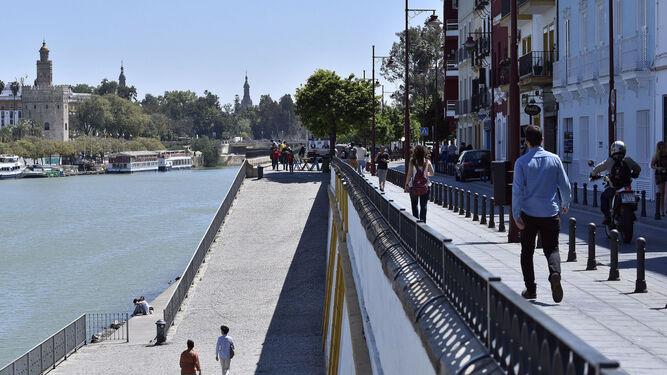 Viandantes pasean por la calle Betis en Triana.