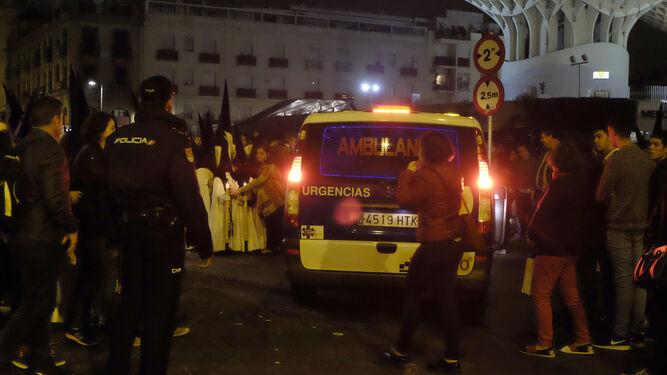 Una ambulancia pasa por el medio de la fila de nazarenos de los Gitanos en la plaza de la Encarnación.