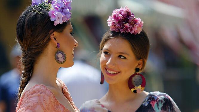 Dos jóvenes flamencas se miran sonrientes.
