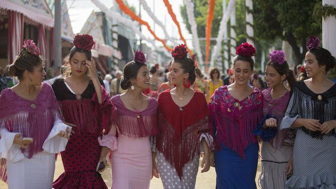 Paseo de mujeres con el real. Todas con el mantón y el clavel en la cabeza. Un cartel vivo de fiestas primaverales.