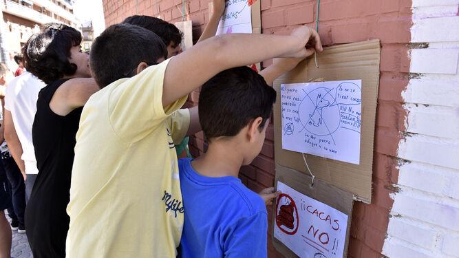 Escolares acaban de colar sus carteles.