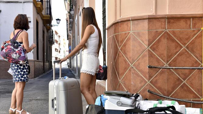 Dos jóvenes aguardan con sus maletas en la calle Jesús de la Vera Cruz.