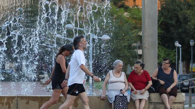 Una pareja que practica deporte pasa junto a una fuente para regular su temperatura.