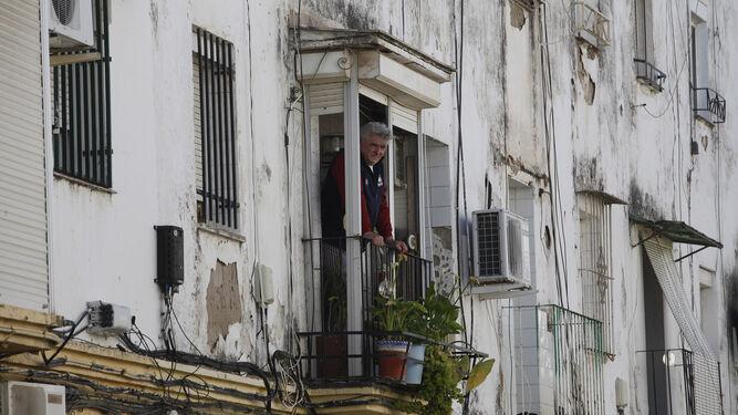 Un hombre observa desde el balcón de su casa el trabajo de la Policía, el pasado 3 de abril, cuando fue asesinada una mujer en la calle Perdiz.