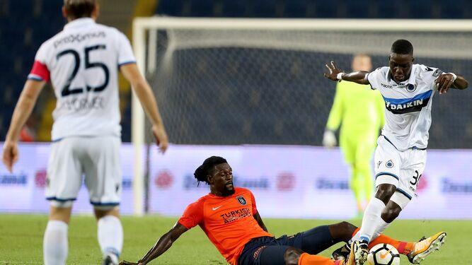 El delantero del Basaksehir Adebayor se lanza al suelo en la disputa del balón con Nakamba, del Brujas.