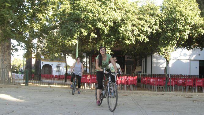 Isabel, junto a dos alumnos que aprenden a montar en bici.