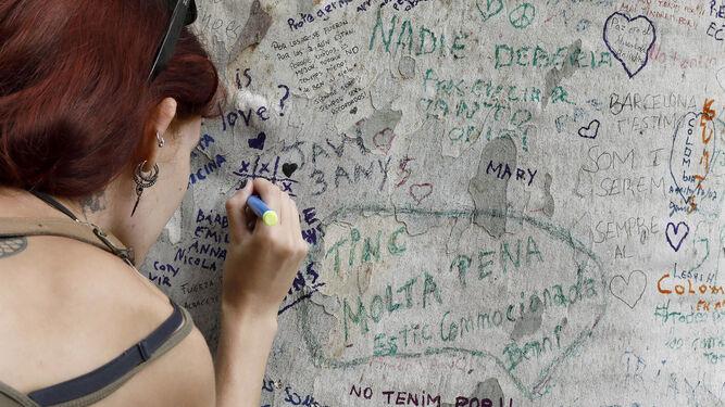 Una persona muestra sus condolencias con un mensaje escrito en un árbol de Las Ramblas.