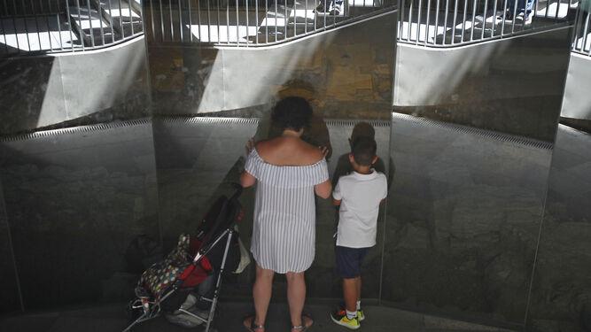 Una familia observa la cripta arqueológica de las 'setas' de la Encarnación desde el exterior, al estar cerrada este mes.