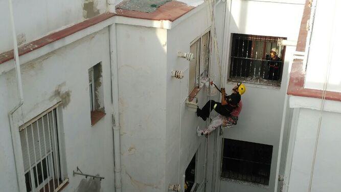Un bombero junto al obrero suspendido en la fachada