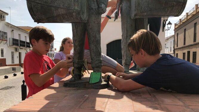 Varios alumnos del CEIP San Pedro de Zúñiga colocan etiquetas con el dinero que cuesta un grupo escultórico.