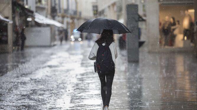 Una joven camina por la calle Velázquez en medio de una gran tormenta