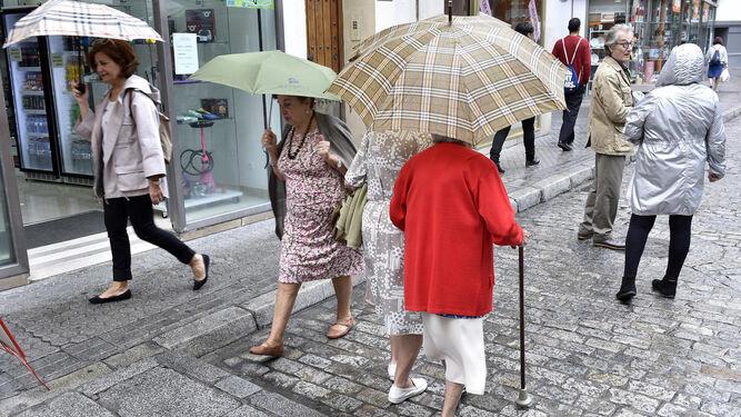 Varias personas con paraguas por el centro