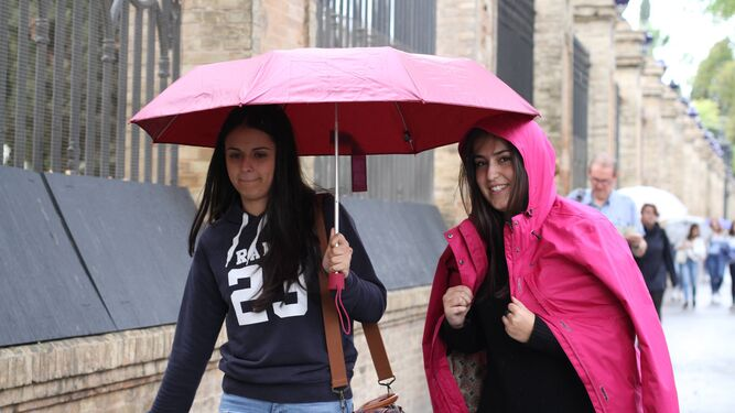 Dos jóvenes se resguardan de la lluvia