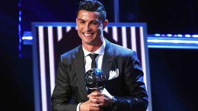 El delantero madridista, sonríe aferrado a su trofeo.