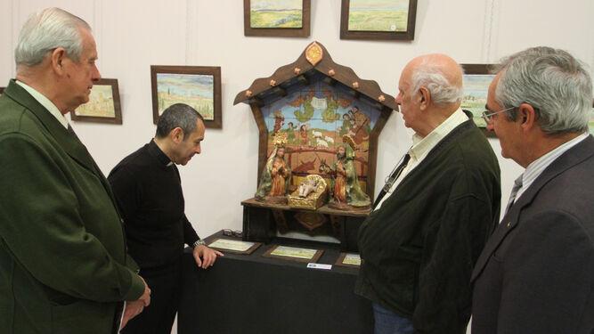 El párroco, Manuel Sánchez, el artista, García Chaparro, y dos directivos del Mercantil junto a un belén.